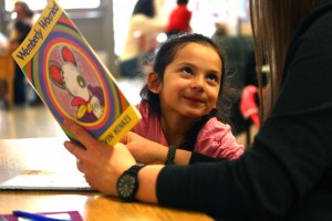 Little girl smiling up at reading volunteer, engaged in reading Wemberly Worried together.