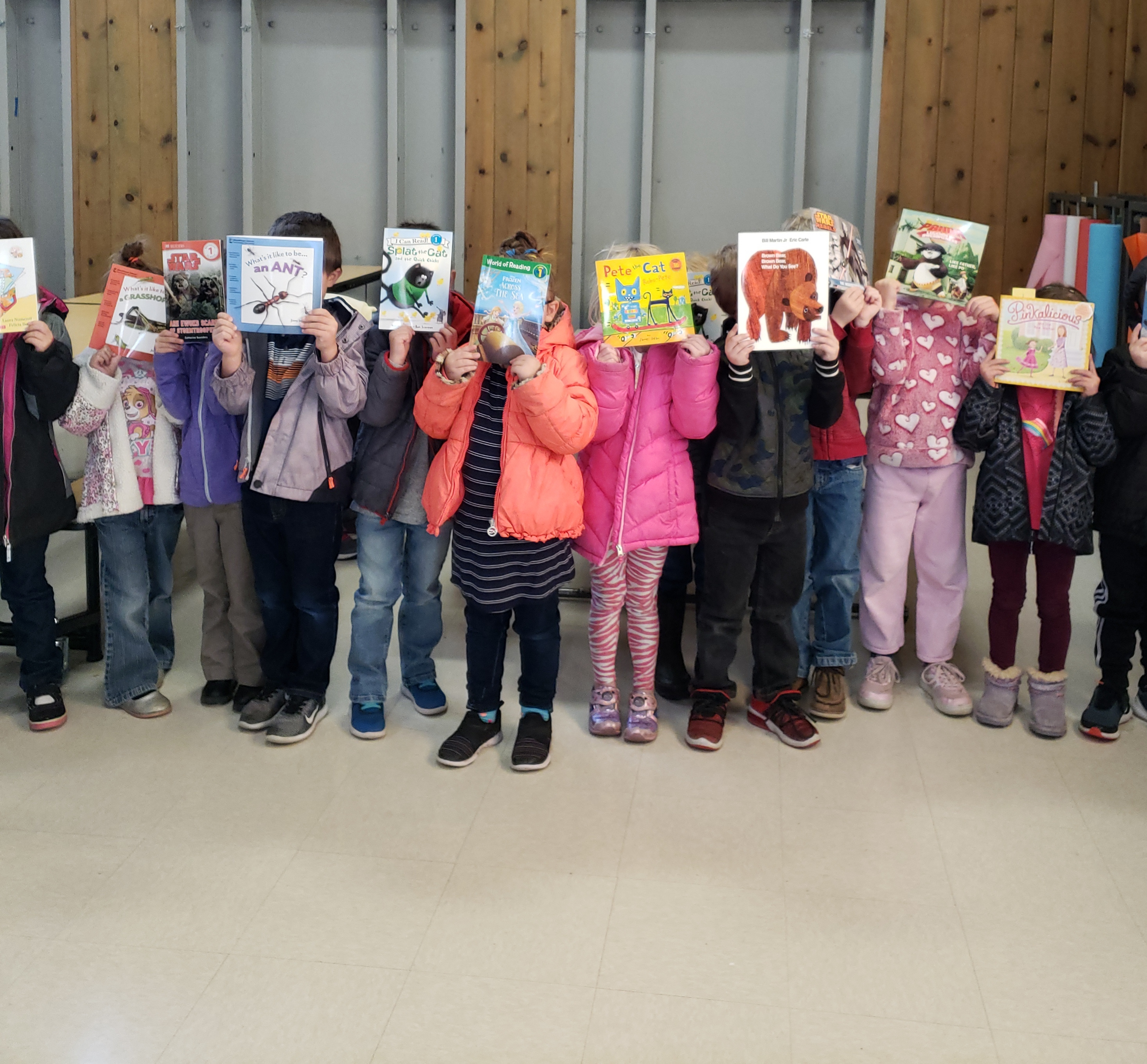 A line of children holding books over their faces