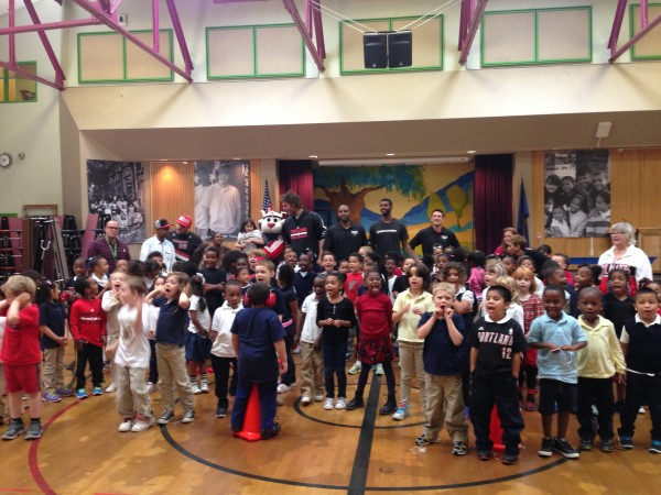 kindergarten through third grade kids with portland trail blazer players and coaches along with mascot Blaze
